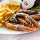 Close up big size grill shrimps with fried potato, vegetables and lemon, lunch time in restaurant - PhotoDune Item for Sale