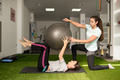 Physical therapist assisting young caucasian woman with exercise - PhotoDune Item for Sale