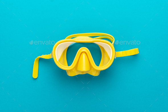 yellow diving mask over blue background with central composition - Stock Photo - Images