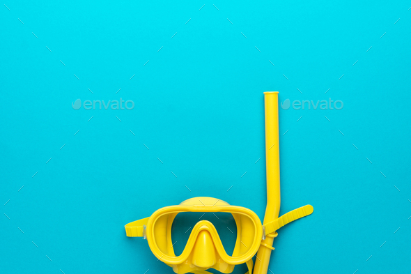 yellow diving mask and snorkel over blue background with copy space - Stock Photo - Images