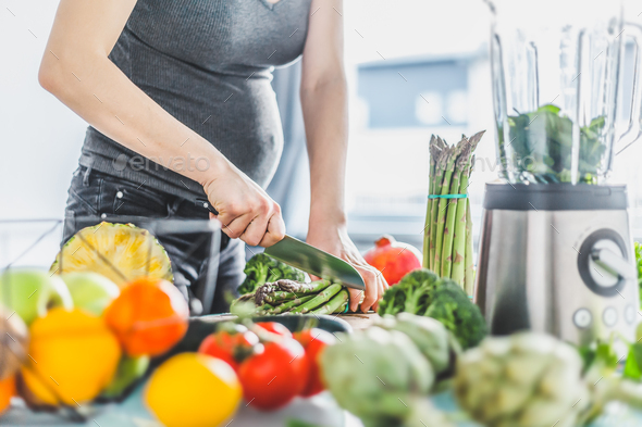 Pregnant woman cooking healthy food - Stock Photo - Images