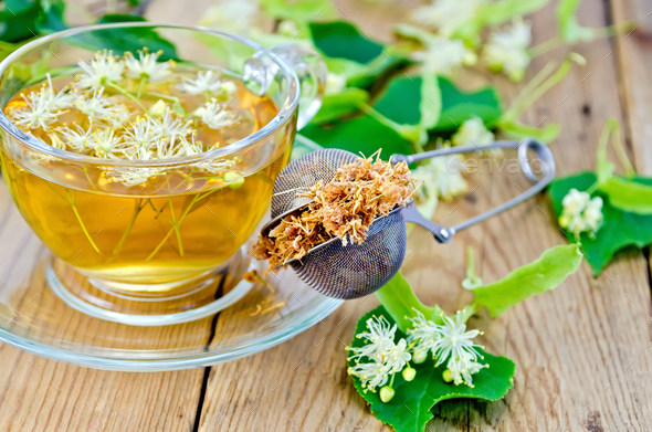 Herbal tea from linden flowers with strainer on board - Stock Photo - Images