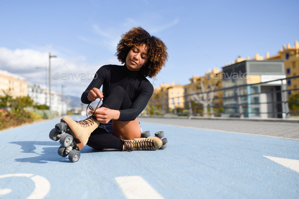 Young smiling black girl sitting on bike line and puts on skates - Stock Photo - Images