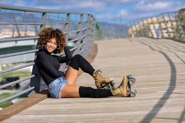 Afro hairstyle woman on roller skates sitting on urban bridge - Stock Photo - Images