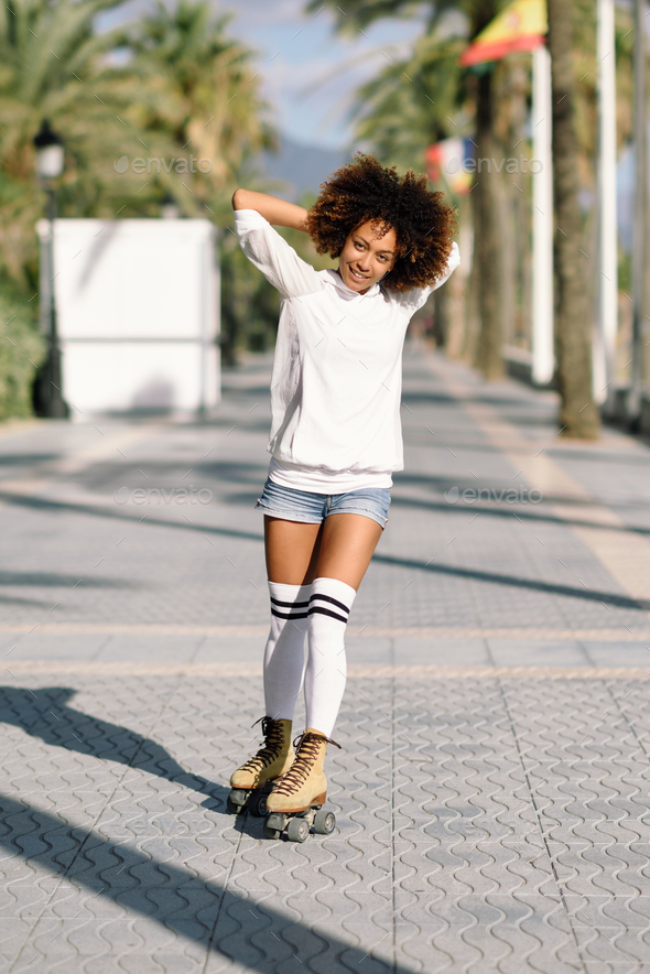 Black woman on roller skates rollerblading in beach promenade wi - Stock Photo - Images