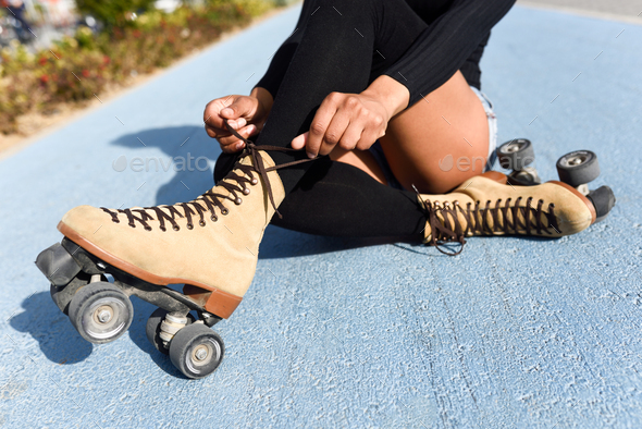 Unrecognizable black girl sitting on bike line and puts on skate - Stock Photo - Images