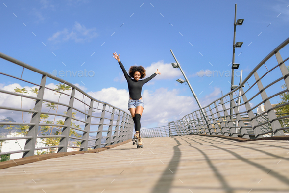 Afro hairstyle woman on roller skates riding outdoors on urban bridge - Stock Photo - Images