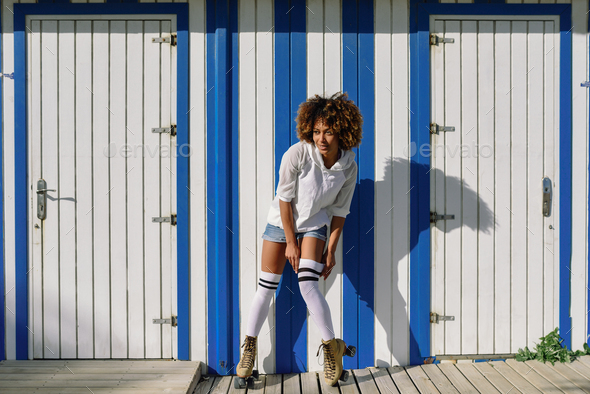 Young black woman on roller skates near a beach hut. - Stock Photo - Images