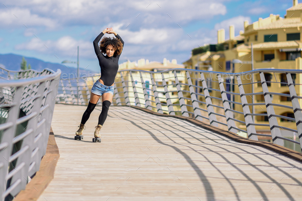 Afro hairstyle woman on roller skates riding outdoors on urban b - Stock Photo - Images
