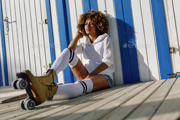 Young black woman on roller skates sitting near a beach hut. - Stock Photo - Images