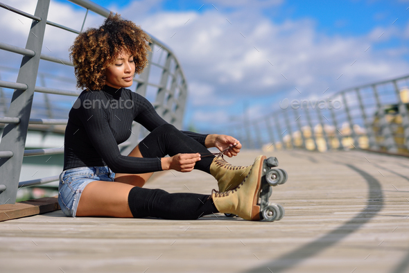 Young smiling black girl sitting on urban bridge and puts on ska - Stock Photo - Images