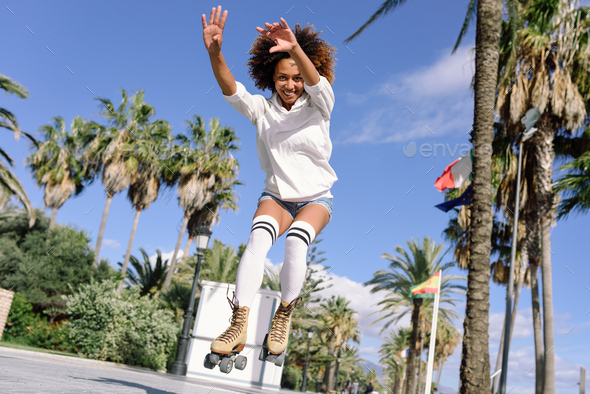 Black woman, afro hairstyle, on roller skates jumping near the b - Stock Photo - Images
