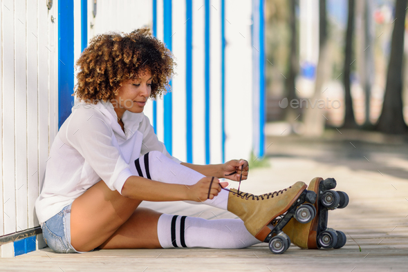 Young black woman sitting on wooden floor puts on skates. - Stock Photo - Images