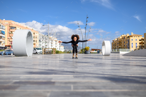 Black woman on roller skates riding outdoors on urban street - Stock Photo - Images