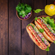 Hot dog with  sausage, cucumber, tomato and lettuce on dark wooden background.  - PhotoDune Item for Sale