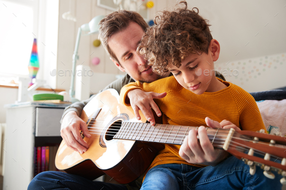 Single Father At Home With Son Teaching Him To Play Acoustic Guitar In Bedroom - Stock Photo - Images