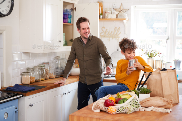 Father And Son Coming Home From Shopping Trip Using Plastic Free Bags Unpacking Groceries In Kitchen - Stock Photo - Images