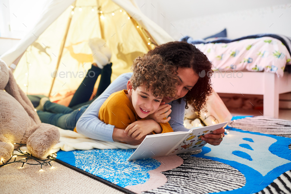 Single Mother Reading With Son In Den In Bedroom At Home - Stock Photo - Images