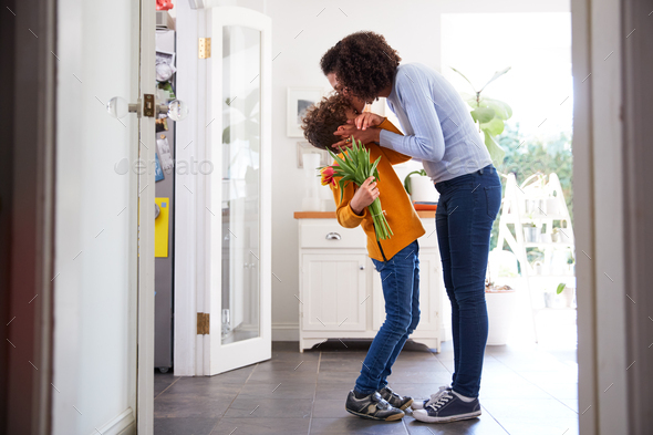 Loving Son Giving Mother Bunch Of Flowers To Celebrate Mothers Day At Home - Stock Photo - Images