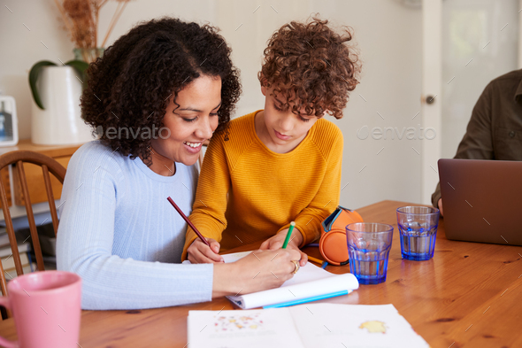 Mother Helping Son With Homework On Kitchen Table At Home - Stock Photo - Images