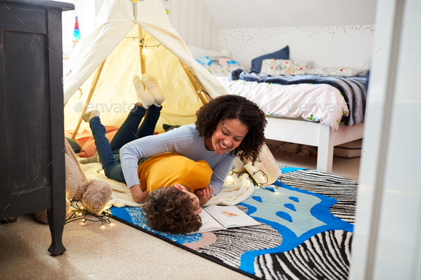 Single Mother Tickling Son As They Read In Den In Bedroom At Home - Stock Photo - Images
