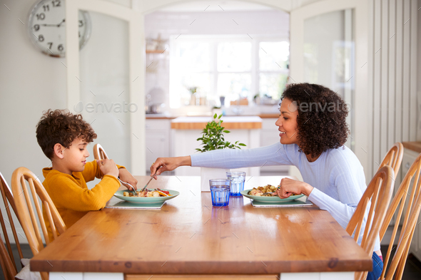 Single Mother Sitting At Table Eating Meal With Son In Kitchen At Home - Stock Photo - Images