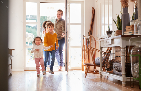 Family Returning Home After Trip Out With Excited Children Running Ahead - Stock Photo - Images