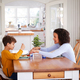Single Mother Sitting At Table Eating Meal With Son In Kitchen At Home - PhotoDune Item for Sale