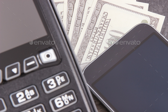 Payment terminal, smartphone with NFC technology and currencies dollar - Stock Photo - Images