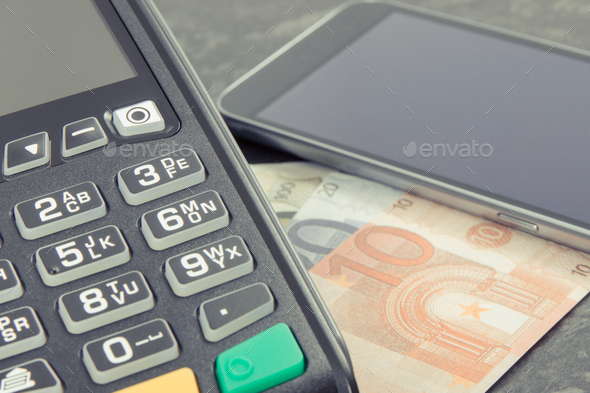 Payment terminal, money and smartphone with NFC technology using for cashless paying - Stock Photo - Images