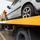 Broken car on flatbed tow truck being transported for repair - PhotoDune Item for Sale