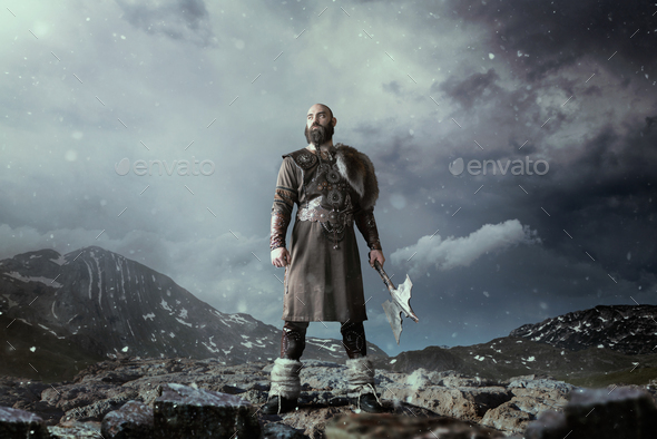 Viking with axe standing in rocky mountains - Stock Photo - Images