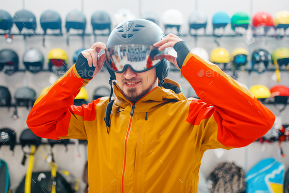 Man trying on helmet for ski or snowboarding - Stock Photo - Images