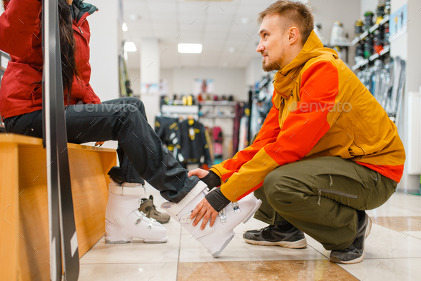 Man helps woman to trying on ski boots, shopping - Stock Photo - Images