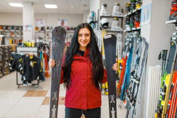Woman at showcase holding downhill ski in hands - Stock Photo - Images