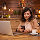 Portrait of a beautiful woman sitting in a coffee shop texting on her phone - PhotoDune Item for Sale