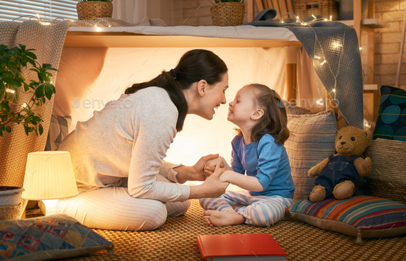 mother and daughter playing in tent - Stock Photo - Images