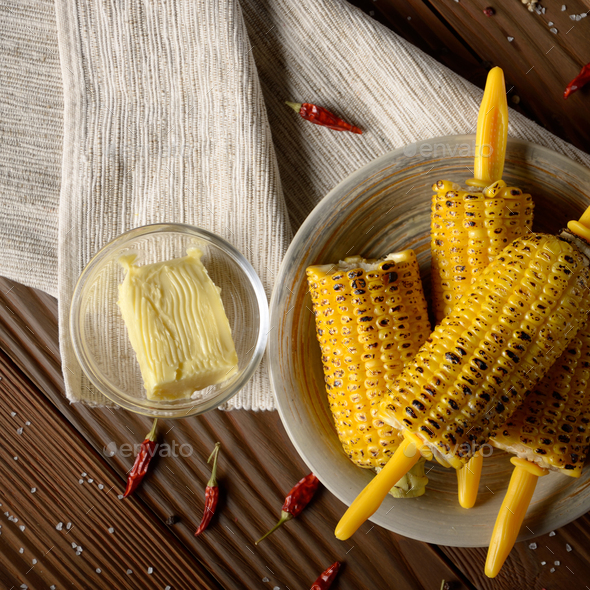 Top view of Wooden table with deep grilled sweet corn cobs under - Stock Photo - Images