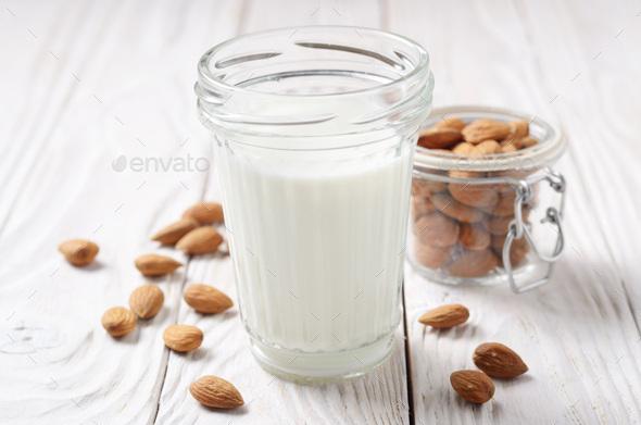 Milk or yogurt in mason jar on white wooden table with almonds i - Stock Photo - Images