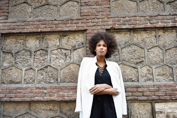 Young black woman with afro hairstyle standing in urban backgrou - Stock Photo - Images