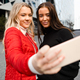 Smiling Beautiful Friends Taking Selfie Through Smartphone In City - PhotoDune Item for Sale