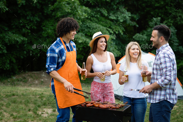 Friends having a barbecue party in nature while having fun - Stock Photo - Images