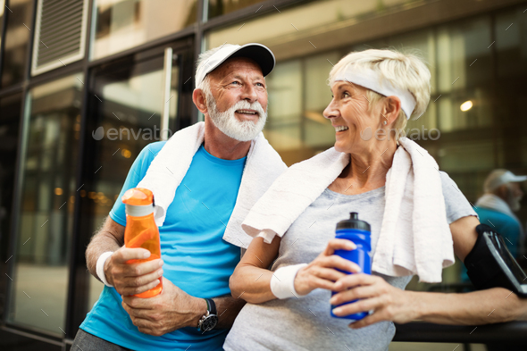 Mature couple jogging and running outdoors in city - Stock Photo - Images