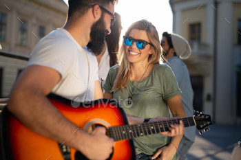 Group of young women friends having fun and playing guitar