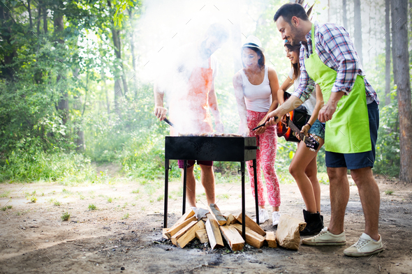 Friends making barbecue and having lunch in the nature - Stock Photo - Images
