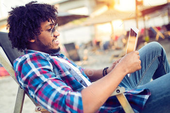 Banking online, portrait of happy black business man with tablet on the beach