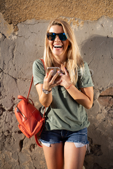 Beautiful smiling woman looking at her cell phone and holding drink