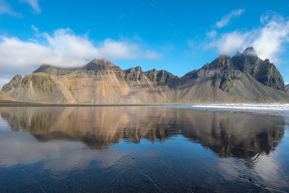 Reflection of Vestrahorn mountain in the waters of the Atlantic ocean. Stokksnes, Hofn, Iceland - Stock Photo - Images