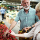 Smiling senior couple buying vegetables and at the merket - PhotoDune Item for Sale