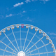 Ferris wheel with one car pink colored against the blue sky. - PhotoDune Item for Sale